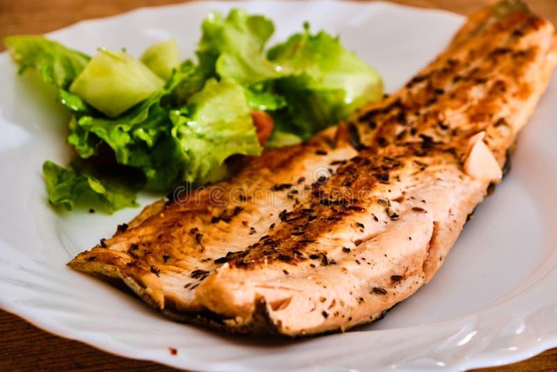 Pstrągowy rybi polędwicowy z warzywami na bielu talerzu zdjęcie stock