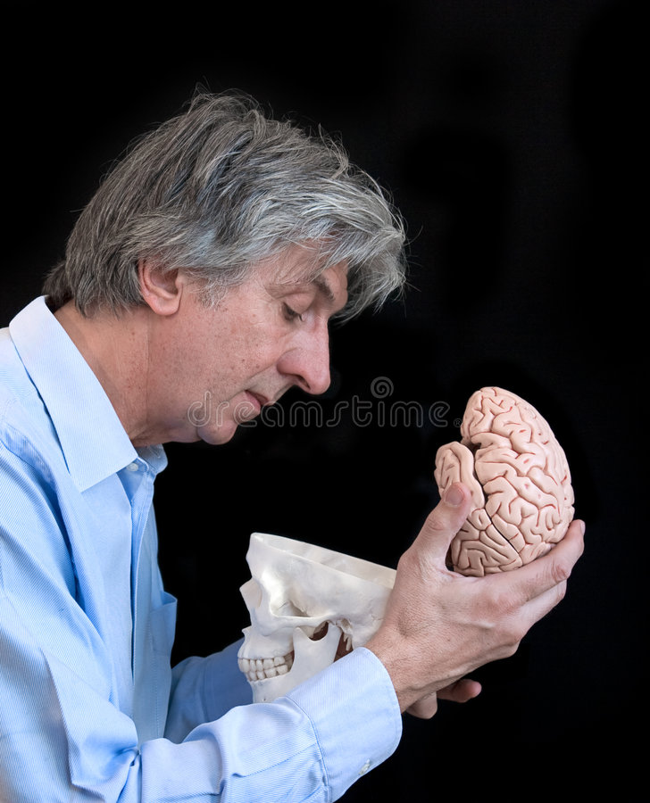 Psy. Profile of a mature man looking in an empty skull with brain in his hand stock image