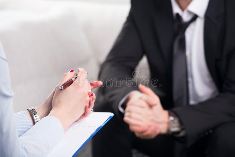 Psychiater die een mannelijke patiënt onderzoekt stock afbeelding