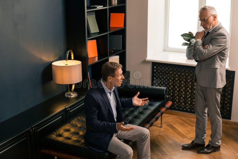 Psychiatre caucasien sérieux écoutant son patient inquiété photos stock