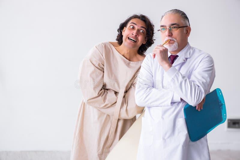 Psychiatre masculin âgé de docteur examinant le jeune patient images stock