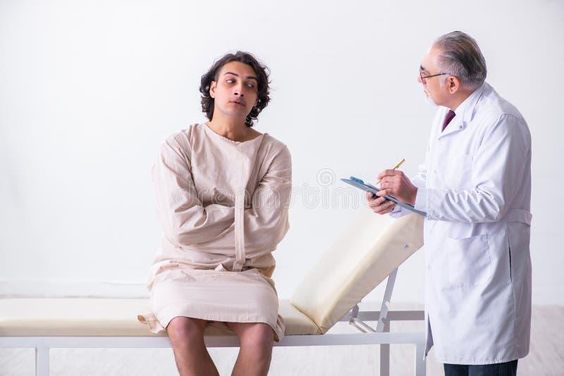 Psychiatre masculin âgé de docteur examinant le jeune patient image stock