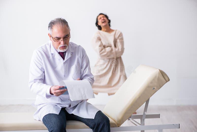 Psychiatre masculin âgé de docteur examinant le jeune patient images libres de droits