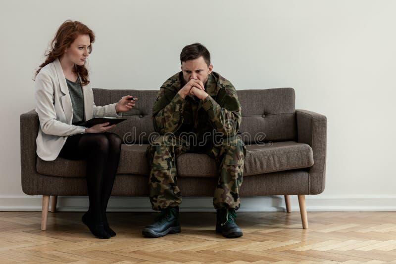 Psychiatre parlant à son patient fâché tout en se reposant sur un sofa photos stock