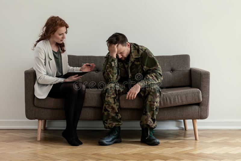 Psychiatre professionnel soutenant le soldat malheureux pendant la consultation photos stock