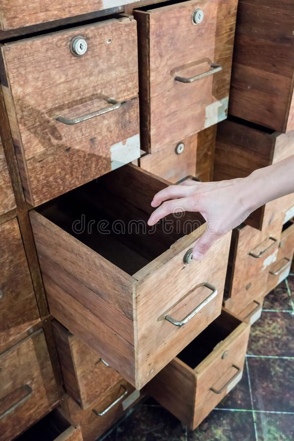 Psychiatric hand opening a drawer of old haunted wooden cabinet. By wall royalty free stock photos