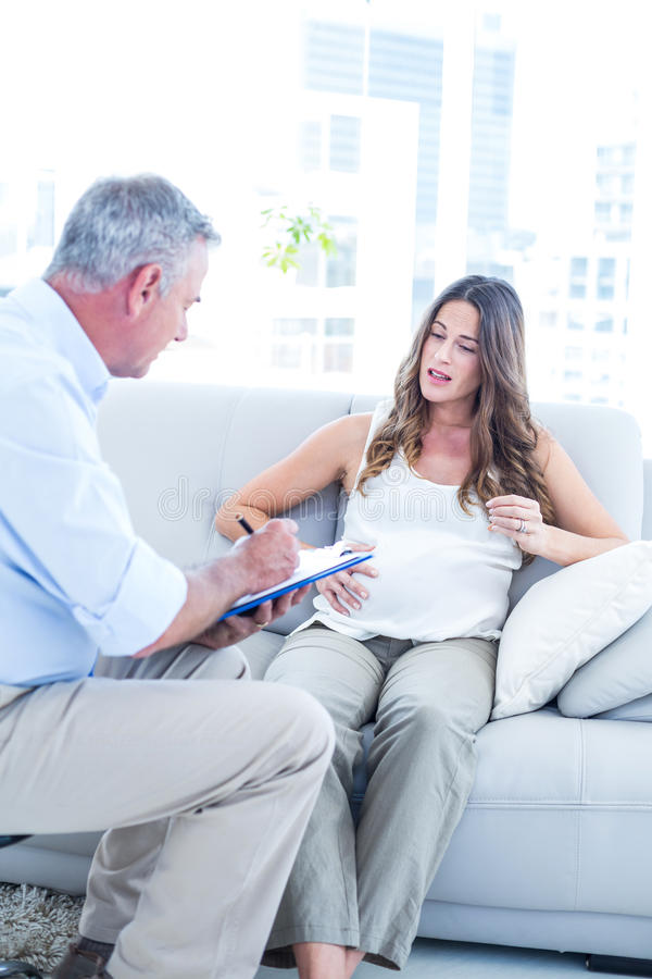 Psychiatrist advising preganant woman at home. Psychiatrist advising preganant women while sitting on sofa at home stock images