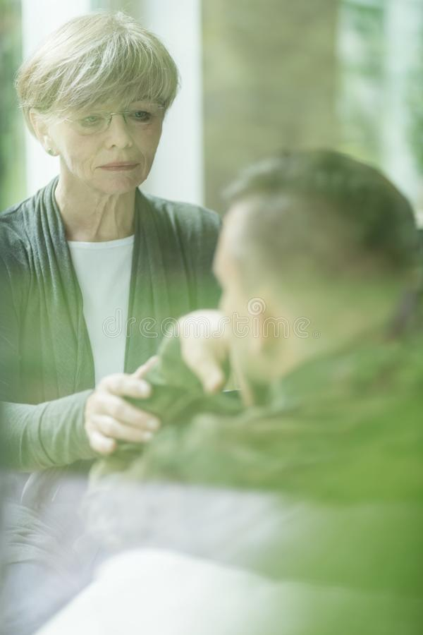 Psychiatrist comforting military patient. Image of female psychiatrist comforting military patient stock photos