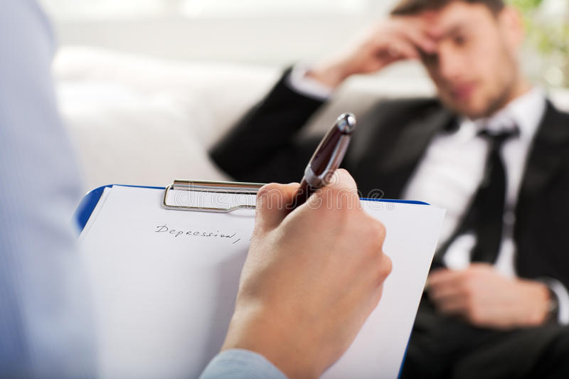 Psychiatrist examining a male patient. Over the shoulder view, of a business man sit on a couch talking to his psychiatrist royalty free stock photography