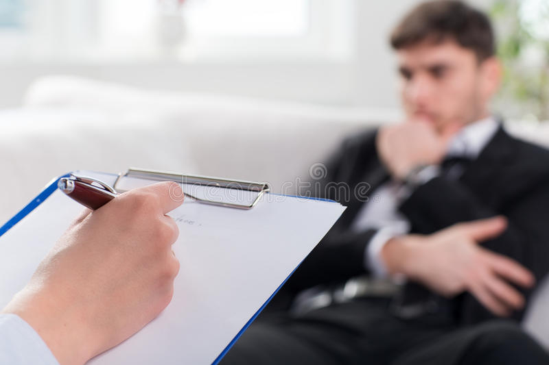 Psychiatrist examining a male patient. Over the shoulder view, of a business man sit on a couch talking to his psychiatrist stock photography