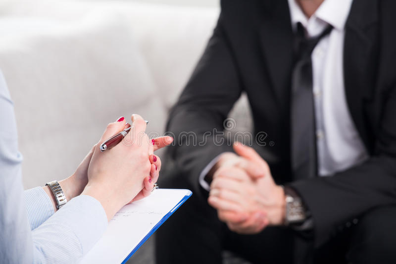 Psychiatrist examining a male patient. Over the shoulder view, of a business men sit on a couch talking to his psychiatrist stock image