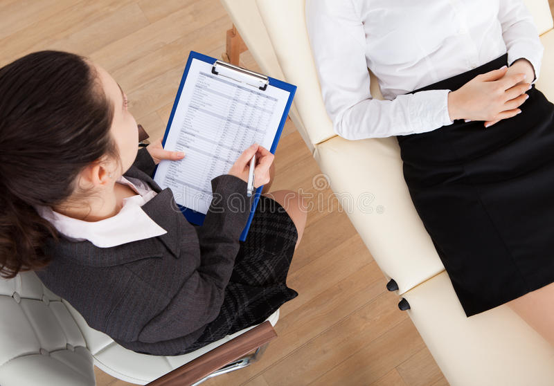 Psychiatrist examining patient. High Angle View Of Psychiatrist Holding Clipboard Examining Businesswoman stock image