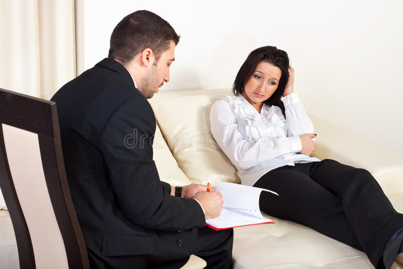 Psychiatrist helps depressed women. Psychiatrist talking with depressed woman patient and trying to help her royalty free stock photos