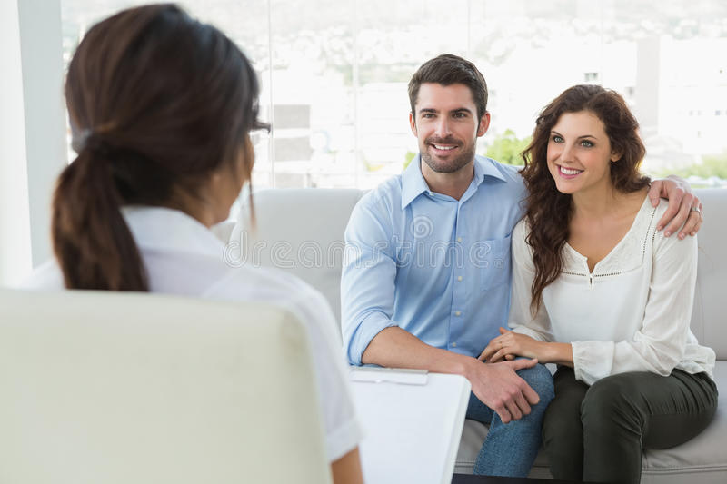 Psychiatrist listening her smiling patients. In the office stock photography