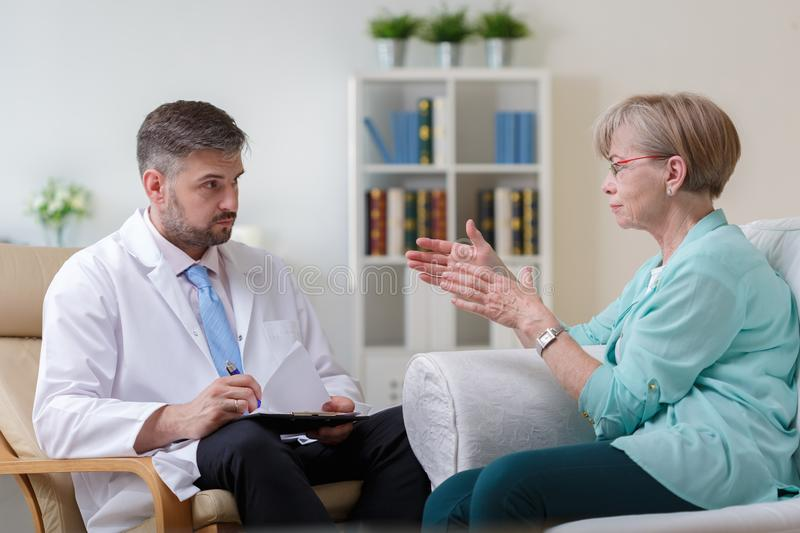 Psychiatrist listening his female patient. Image of psychiatrist listening to his female patient with depression royalty free stock images