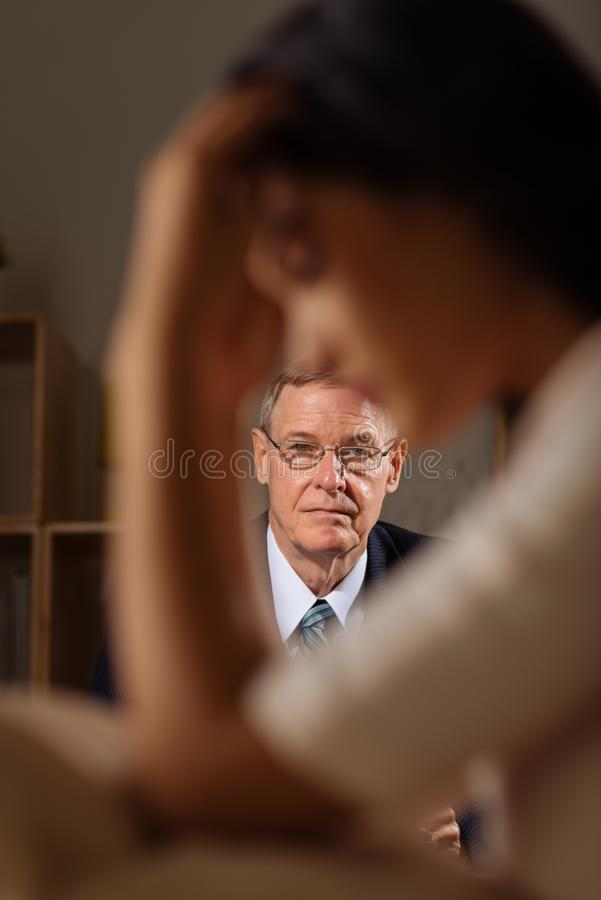 Psychiatrist listening to patient. Professional senior psychiatrist listening to female patient suffering from anxiety royalty free stock photo