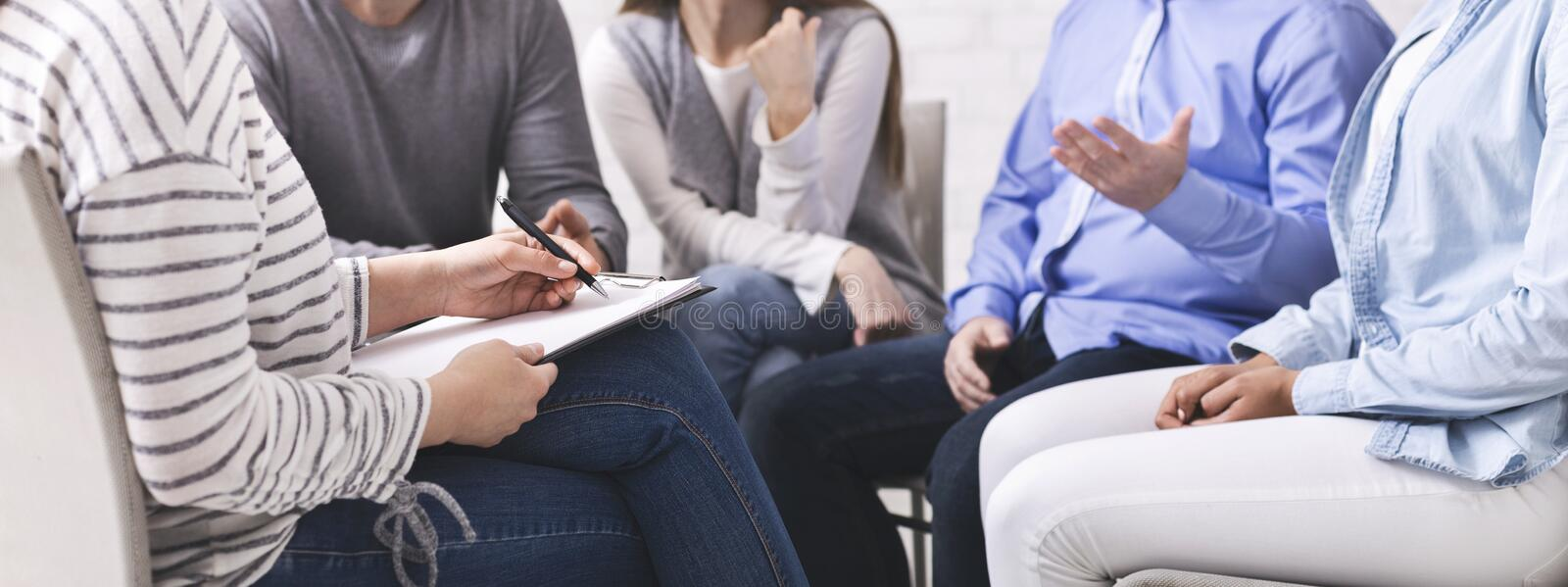 Psychiatrist listening to patients, noting down to clipboard stock images
