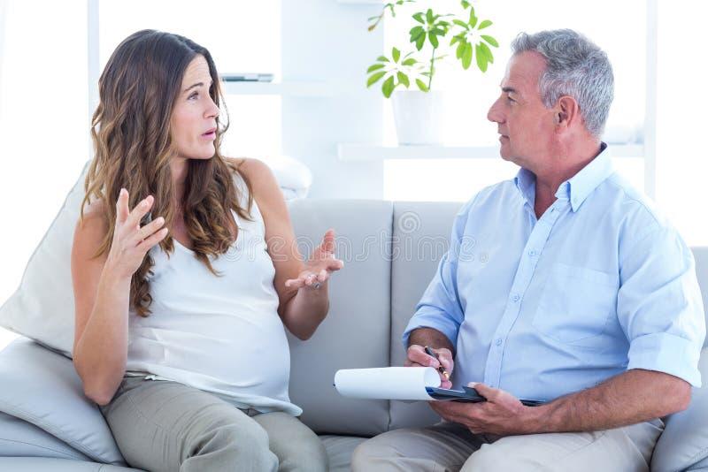Psychiatrist listning pregenat woman in clinic royalty free stock images