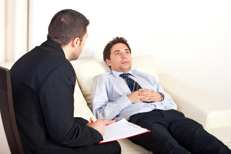 Psychiatrist with male patient. Psychiatrist man talking with hypnotized male patient royalty free stock photography