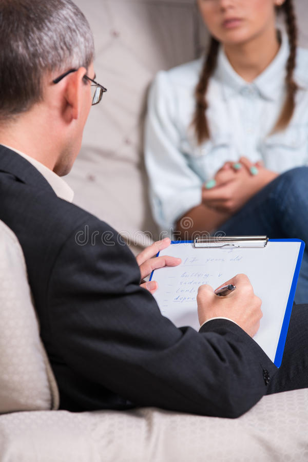 Psychiatrist and patient Teenage girl. Therapist is taking notes during therapy session royalty free stock image