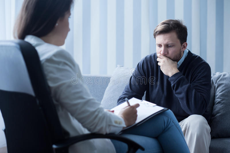 Psychiatrist or psychotherapist. Female psychiatrist or psychotherapist talking with patient stock photos