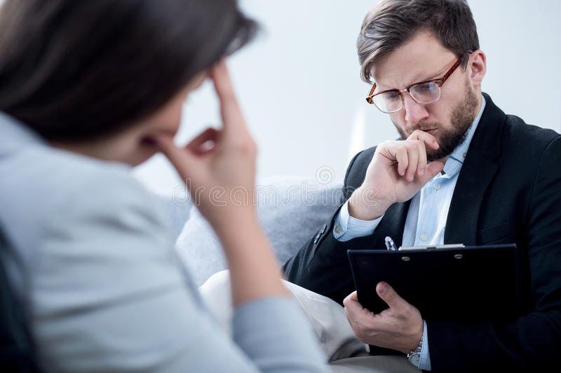Psychiatrist talking with despair businesswoman. In his office stock photography