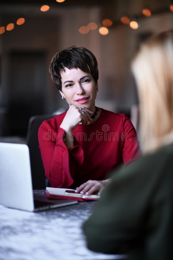 Psychiatrist woman doctor listens a young woman her patient carefuly on her emotional problem or living situation stock photo