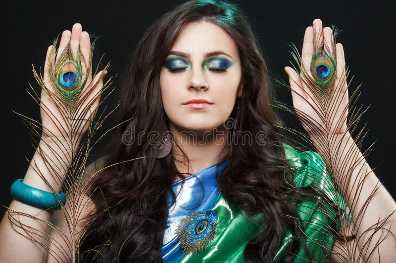 Psychic abilities psychics communicate with spirits. Beauty portrait of girl holding peacock feathers, bright clothes stock photo