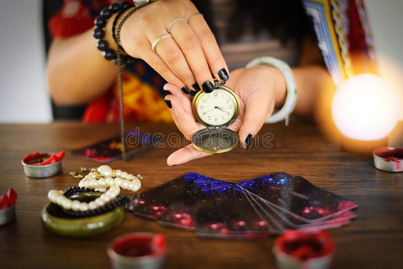Psychic readings and clairvoyance concept - Crystal ball fortune teller with hands hold retro pocket watch and Tarot cards reading. Psychic readings and royalty free stock images