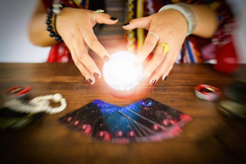 Psychic readings and clairvoyance concept - Crystal ball fortune teller hands and Tarot cards reading divination. Psychic readings and clairvoyance concept / stock image