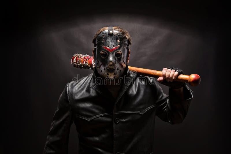 Psycho killer in hockey mask on black background. stock photo