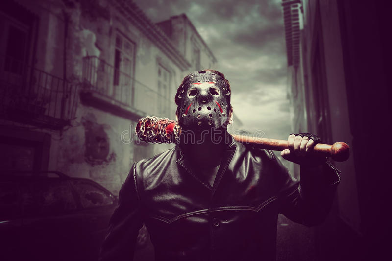 Psycho man in hockey mask with bloody baseball bat stock image