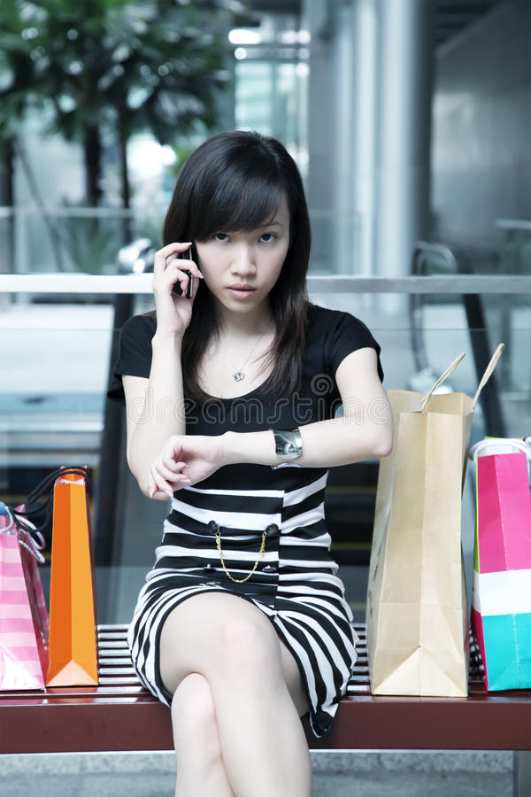Psycho Shopper. Psycho Asian Female Shopper Serious and Waiting royalty free stock images