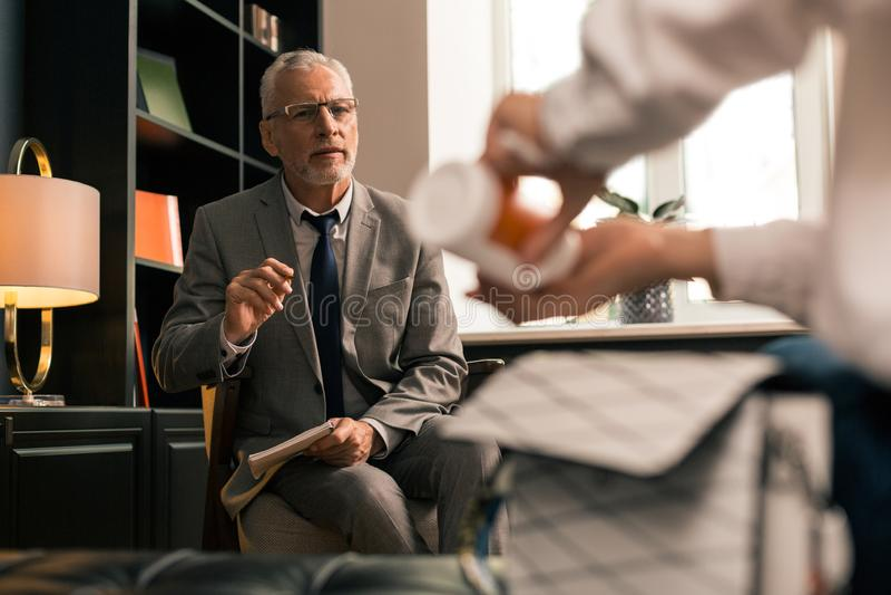Psycholog ogląda blisko jego żeńskiego pacjenta brać antidepressants zdjęcia stock