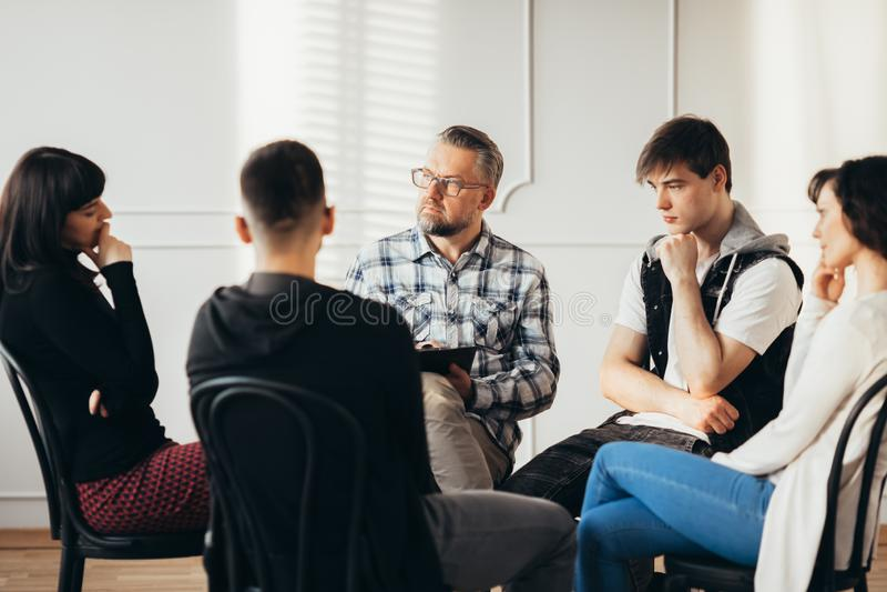 Psychologe, der mit süchtigen Jugendlichen während der Rehabilitation in der Nervenklinik arbeitet lizenzfreie stockfotos