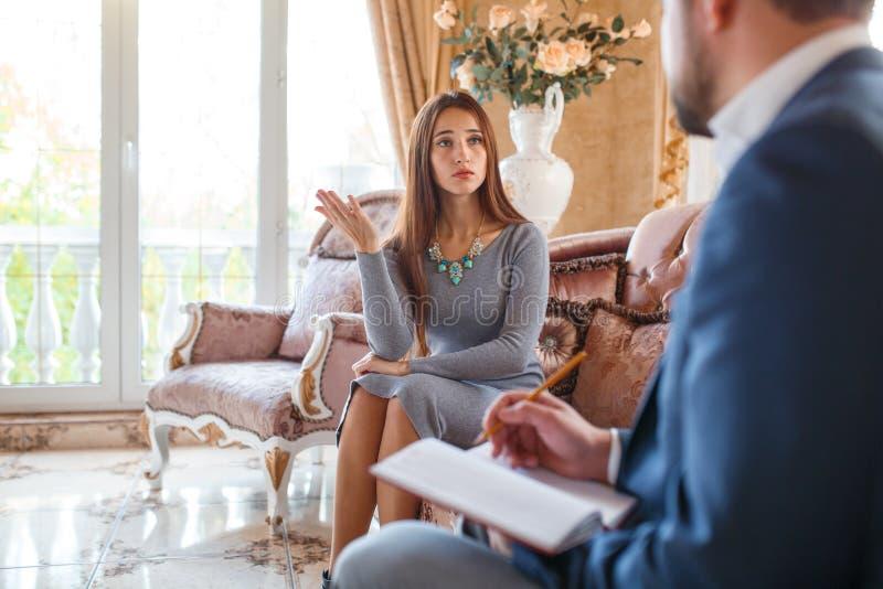 An Psychologen A sagt das Mädchen, das auf der Couch sitzt, dem Doktor ihren Problemen lizenzfreies stockbild