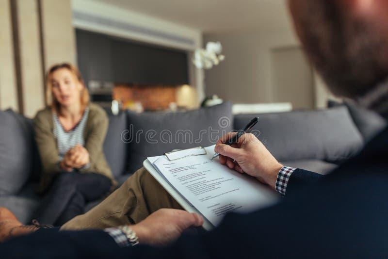 Psychologeschreibensanmerkungen während einer Therapie-Sitzung mit Patienten lizenzfreie stockfotos