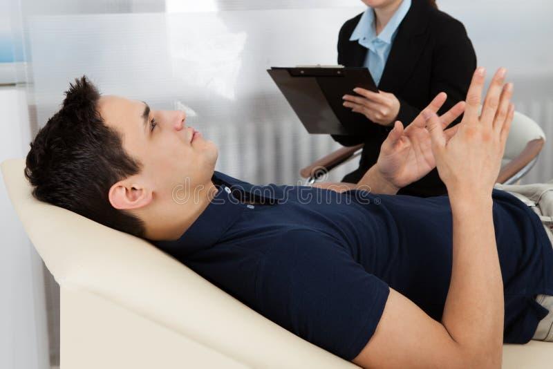 Psychologeschreibensanmerkungen während Patient, der auf Bett liegt lizenzfreie stockbilder