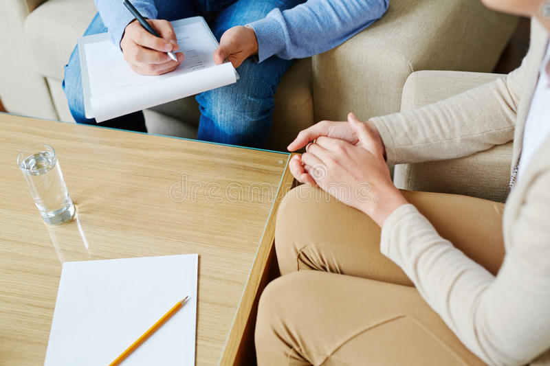 Psychological consultation. Counselor making notes while listening to woman royalty free stock photo