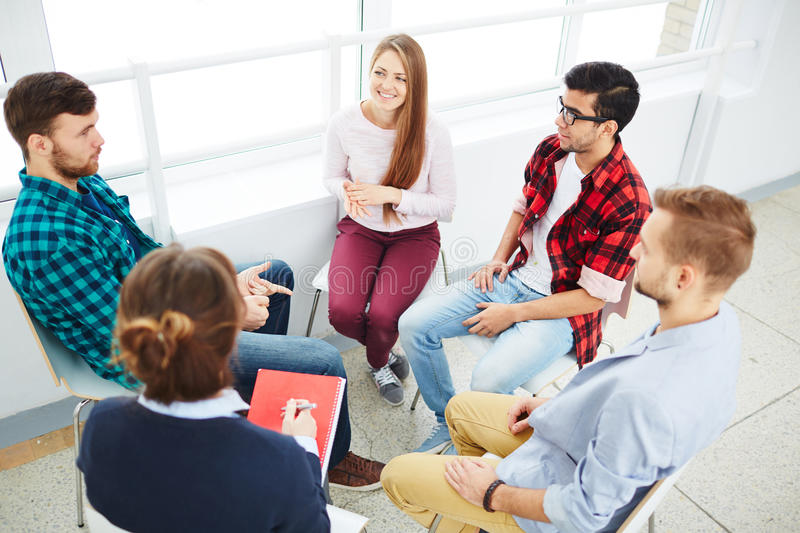 Psychological guidance. Guidance group listening to young man stock image