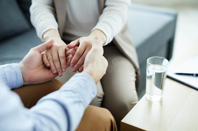 Psychological help. Hands of contemporary counselor holding those of his patients while both sitting by table with glass of water on edge stock image