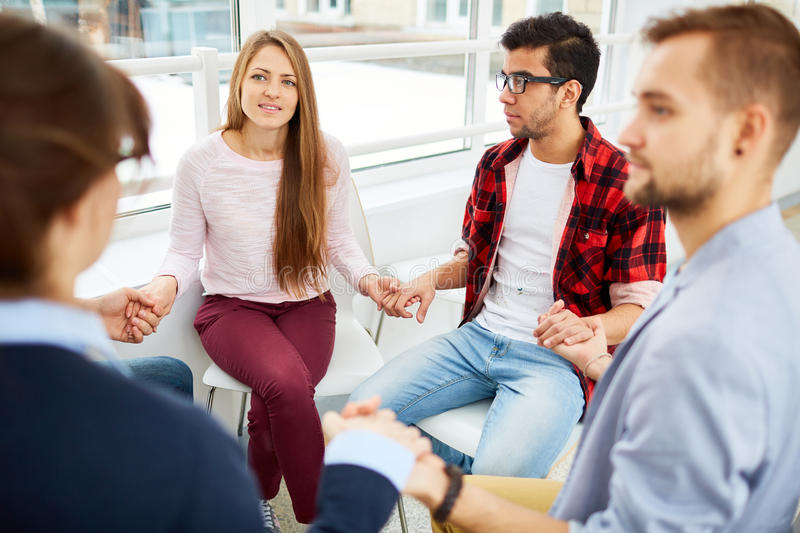 Psychological session. Group of guys and girls holding by hands during psychological session royalty free stock images