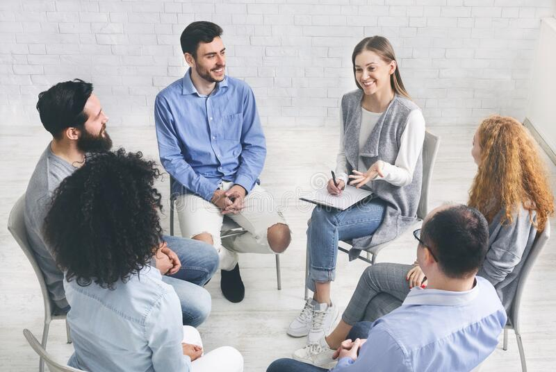 Diverse happy people sitting in trust circle on therapy session royalty free stock image