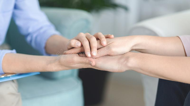 Psychologist consoling her client, holding her hands royalty free stock photo