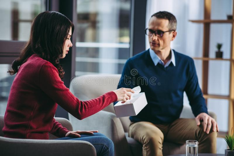 Psychologist giving napkin to upset woman stock photo