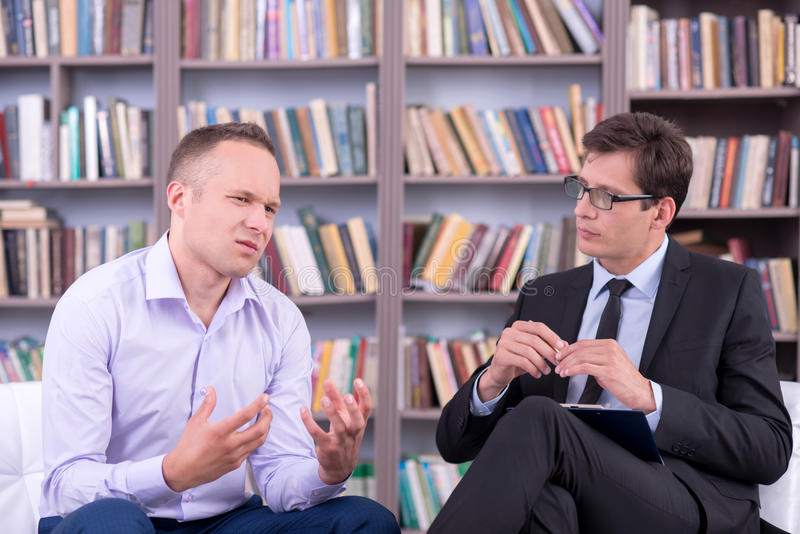 Psychologist listening his male patient at office royalty free stock image