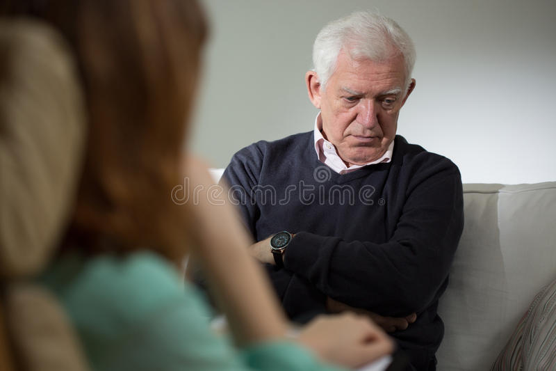 Psychologist listening senior man stock photography