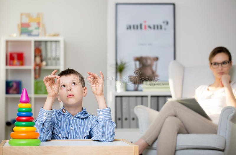 Psychologist observing autistic boy stock image