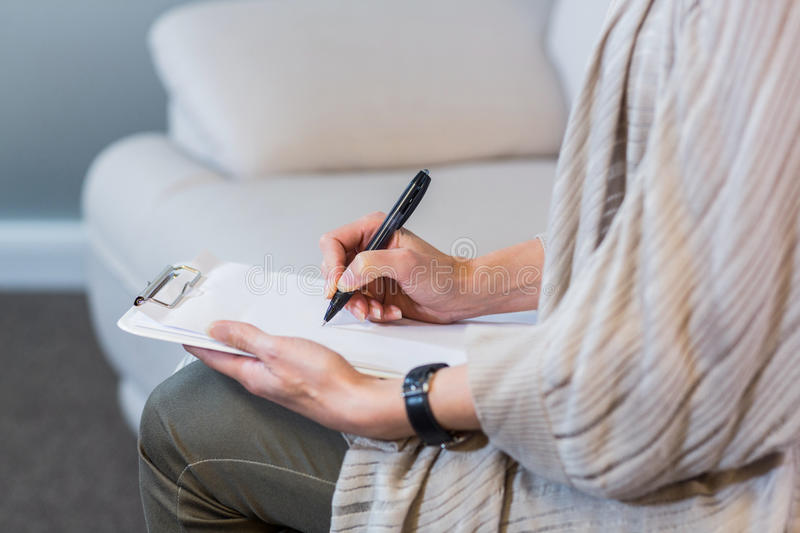 Psychologist sitting on the couch and taking notes stock image