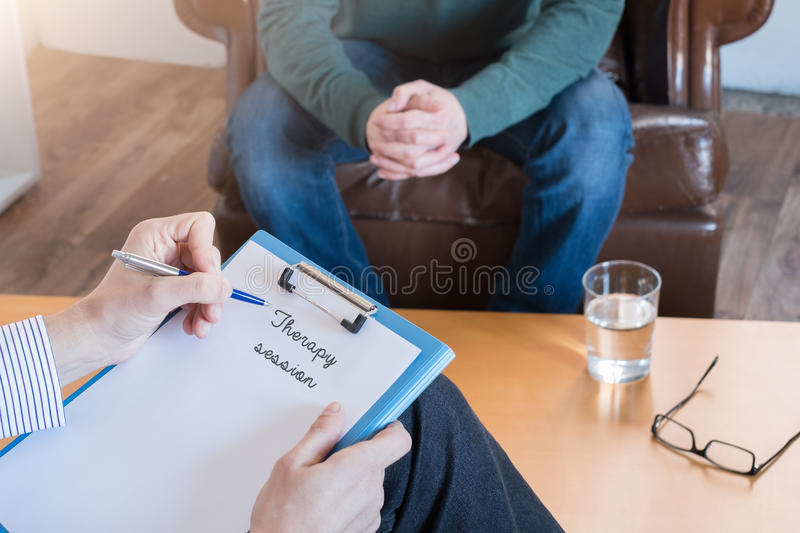 Psychologist taking notes during psychotherapy royalty free stock photography